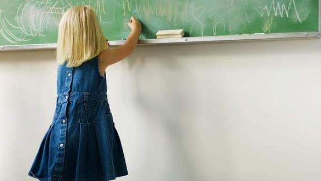 Una niña dibuja en una pizarra de su colegio.