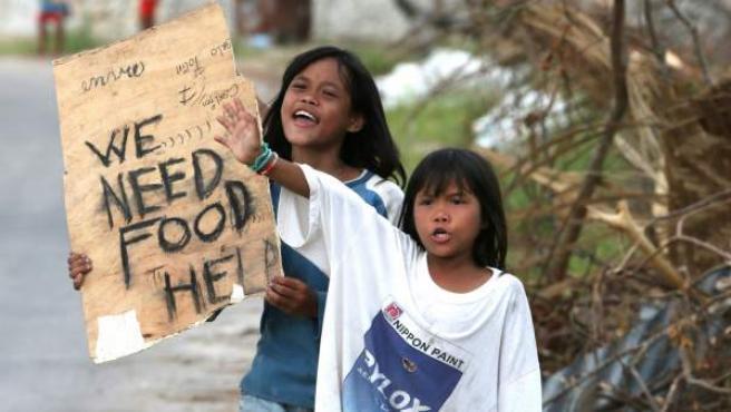 Dos niñas muestran un cartel pidiendo comida en Filipinas.