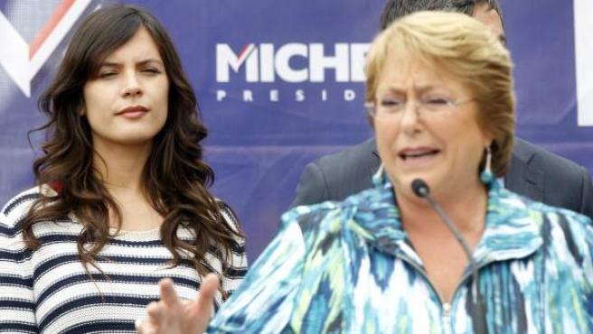 La candidata presidencial por la Nueva Mayoría, Michelle Bachelet (d), habla delante de la diputada electa, Camila Vallejo (i), en un acto de campaña en Santiago de Chile.