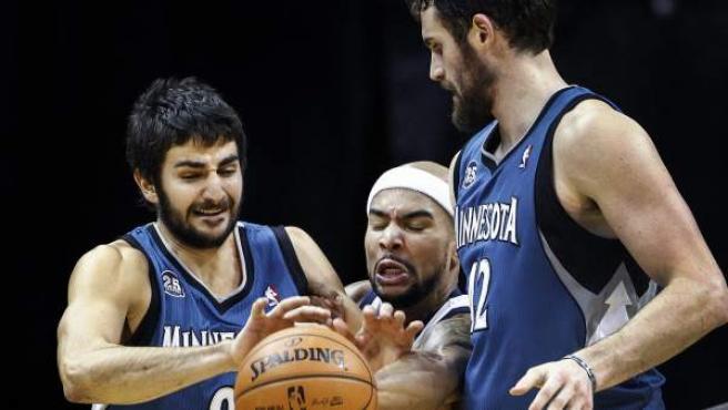 Los jugadores Ricky Rubio y Kevin Love de los Timberwolves de Minnesota ante Jerryd Bayless de los Grizzlies de Memphis.