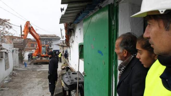 Vecinos de El Ventorro, operarios y policías observan cómo derriban las chabolas del poblado.