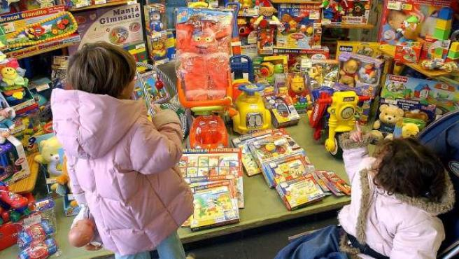 Dos niñas observan un escaparate lleno de juguetes.