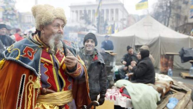 Un hombre ataviado de cosaco fuma en pipa en una protesta contra el Gobierno ucraniano.