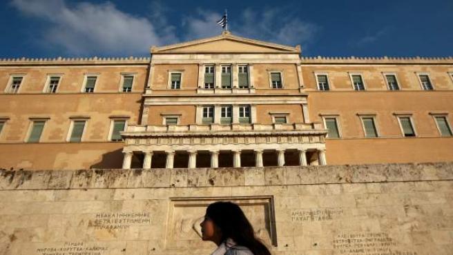 Una joven pasa ante la tumba del soldado desconocido, frente al Parlamento en Atenas, Grecia.