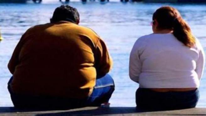 Dos personas obesas descansan sentadas.