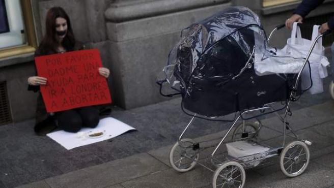 """Una mujer pasa con un carrito de bebé junto a una activista que sostiene un cartel que dice """"dadme una ayuda para ir a Londres a abortar"""", como protesta contra la nueva ley del aborto del Gobierno del PP."""