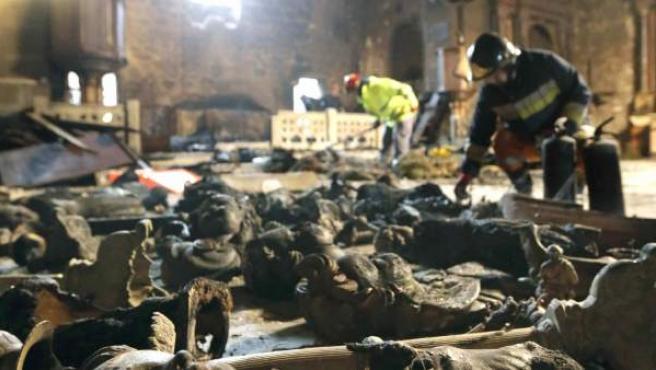 Los bomberos retiran este viernes las figuras y restos del altar que resultó calcinado en el incendio del santuario de A Virxe da Barca.