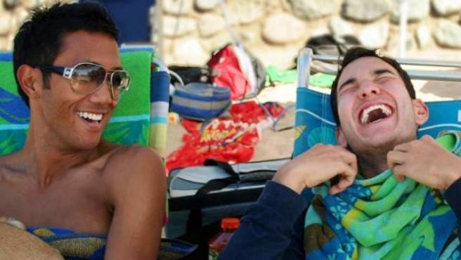 Dos jóvenes ríen a carcajadas en la playa.