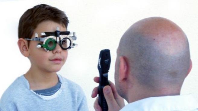 Un optometrista graduando la vista a un niño.