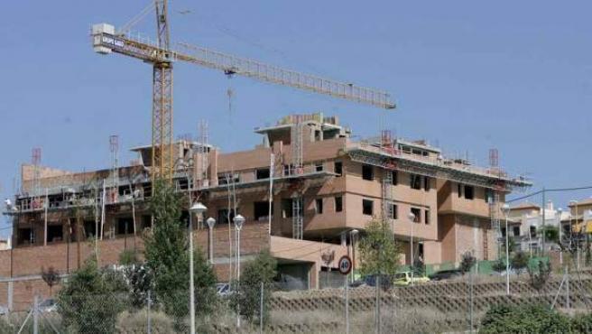 Una grúa sobre el perfil de un edificio en construcción.