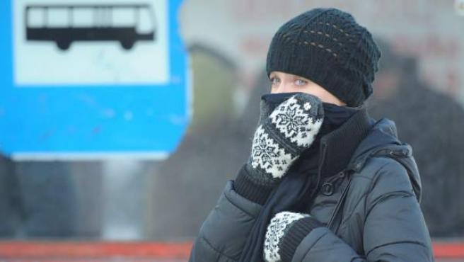 Una mujer, muy abrigada, se cubre el rostro para protegerse del frío.