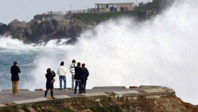 Varias personas observan las olas entrando en la playa de Riazor de A Coruña, donde hay una alerta roja en el mar por olas de hasta nueve metros según fuentes del servicio meteorológico.