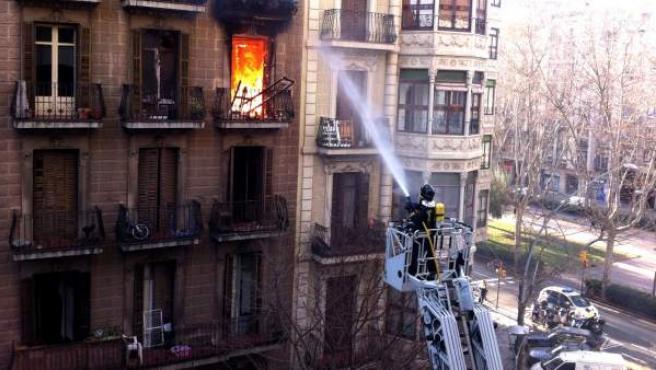 Un bombero intenta sofocar el incendio que ha calcinado un piso del Eixample de Barcelona, en el que ha fallecido un hombre de 78 años.