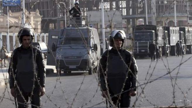 Policías antidisturbios egipcios permanecen tras una alambrada de espino durante antes de ser suspendida la segunda sesión del juicio contra el expresidente egipcio Mohamed Mursi en la Academia de Policía.
