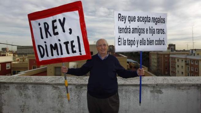 Martín Sagrera posa con las dos pancartas que ha exhibido estos días por las calles de Madrid.