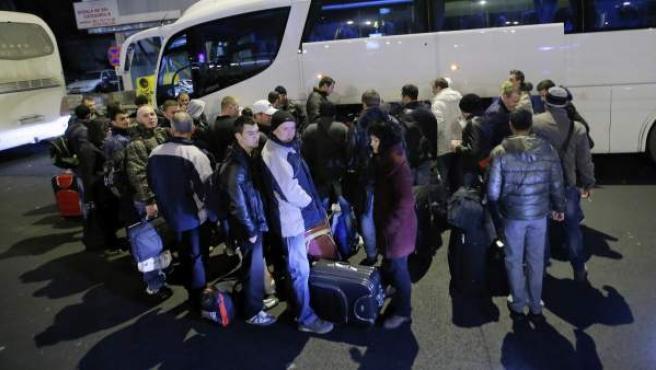Un grupo de rumanos coloca su equipaje en un autobús que los llevará desde Bucarest hasta Bélgica.
