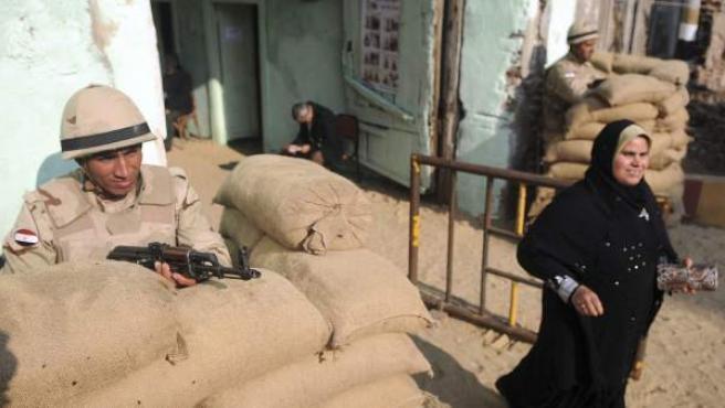 Un soldado observa a una mujer que abandona un colegio electoral egipcio.