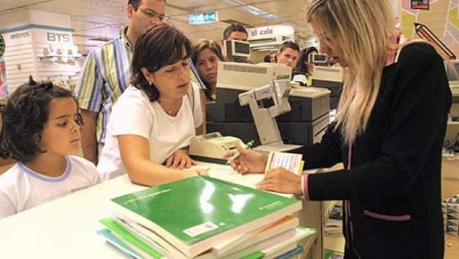 Una mujer compra libros de texto.
