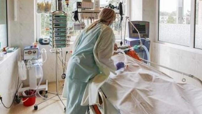 Una médico atiende a un paciente entubado.