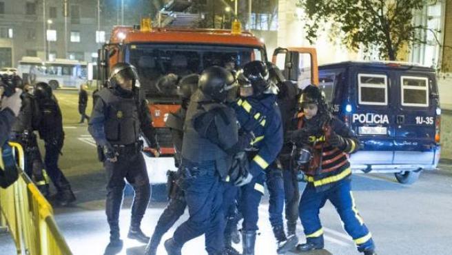 Momento en que la Policía detiene a un bombero durante la manifestación de apoyo a los vecinos de Gamonal en Madrid.
