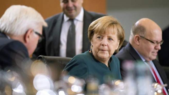 La canciller alemana, Angela Merkel (centro), conversa con el ministro germano de Exteriores, Frank-Walter Steinmeier (izda), durante el Consejo de Ministros celebrado en la Cancillería en Berlín.