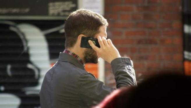 Un chico habla por el teléfono móvil.