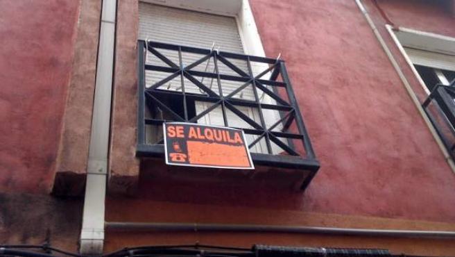 El cartel de Se Alquila en la ventana de una vivienda.