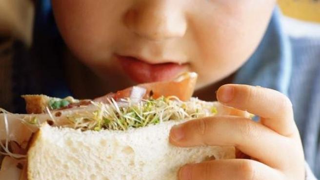 Imagen de un niño comiendo un bocadillo.