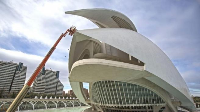 Dos operarios trabajan, desde una plataforma elevadora, en la retirada del revestimiento de la cubierta del Palau de les Arts tras los desprendimientos del pasado mes de diciembre que han obligado a cerrar el auditorio de ópera de Valencia.