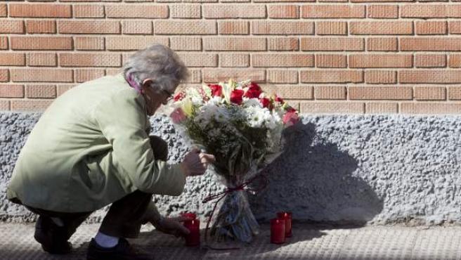 Una vecina coloca flores en la calle Cartago de Córdoba donde un hombre de 36 años y miembro de la plataforma Stop Desahucios, se ha lanzado al vacío desde una cuarta planta.