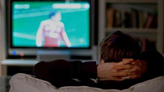 Una persona sentada en el sofá viendo la televisión.