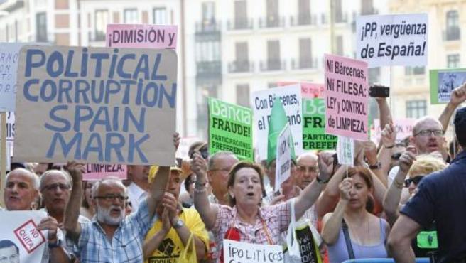 Un grupo de manifestantes protestan frente a la sede del PP contra la corrupción, los bancos y los partidos políticos.
