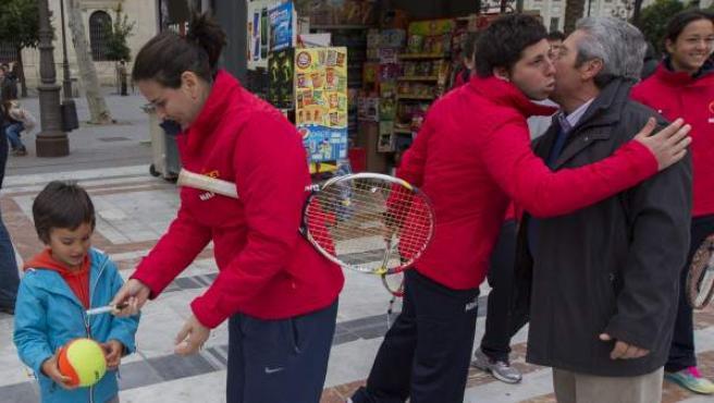 Conchita Martínez, capitana del equipo español de la Copa Federación de tenis, firma un autógrafo mientras Carla Suárez besa a un aficionado en Sevilla.
