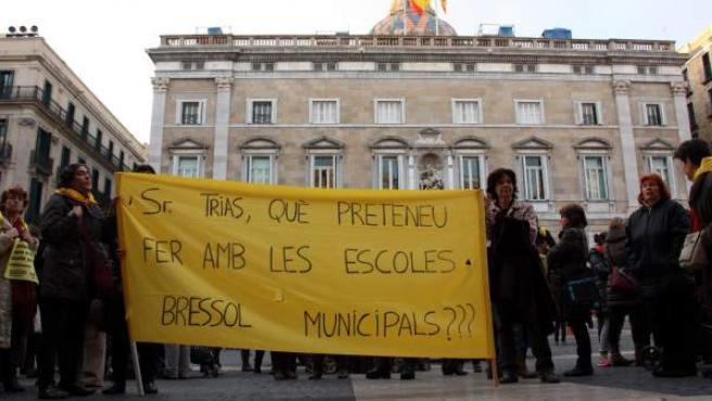 Desenes de persones en una protesta a favor de les escoles bressol municipals davant l'Ajuntament de Barcelona.