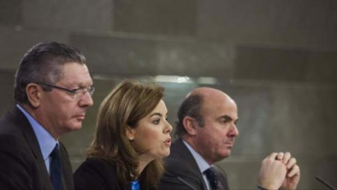 El ministro de Justicia, Alberto Ruiz Gallardón, la vicepresidenta del Ejecutivo, Soraya Sáenz de Santamaría y el titular de Economía, Luis de Guindos (i a d), durante la rueda de prensa posterior a la reunión del Consejo de Ministros.