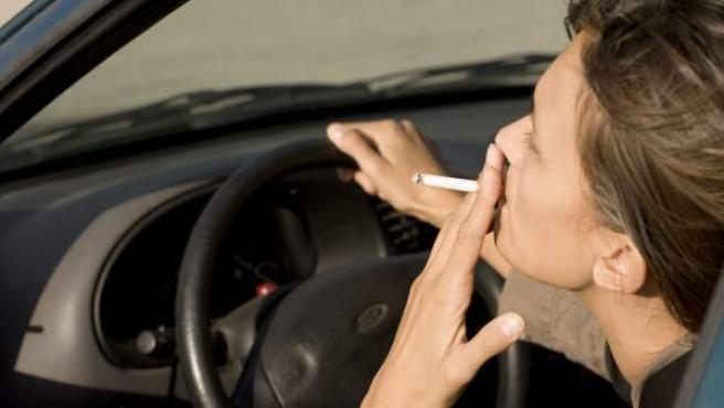 Una mujer fumando en el coche.
