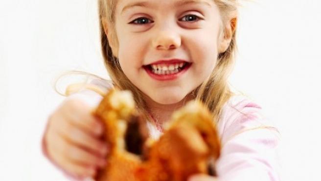 Una menor sonríe mientras come una hamburguesa.