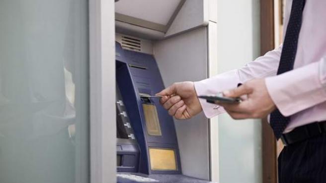 Un hombre saca dinero de un cajero automático.