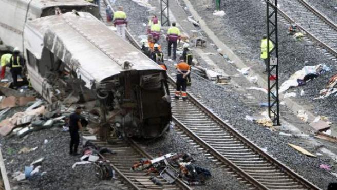 Los servicios de emergencia trabajan junto a las vías tras el accidente del tren Alvia que cubría la ruta entre Madrid y Ferrol y que descarriló cuando ya estaba muy cerca de Santiago de Compostela.