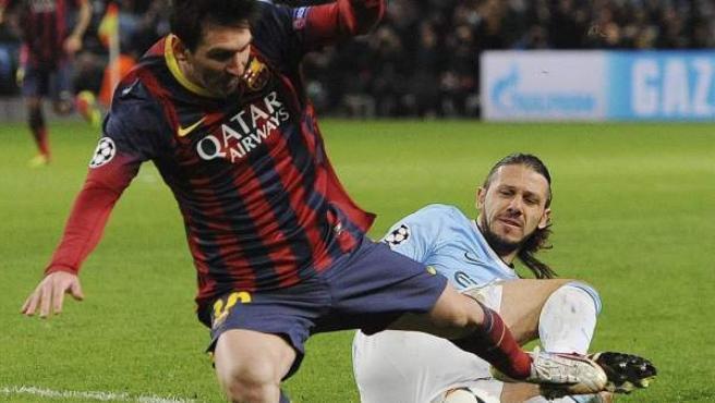 El defensa argentino del Manchester City, Martín Demichelis (d) comete penalti sobre delantero argentino del FC Barcelona, Leo Messi (i) durante el partido de ida de octavos de final de la Liga de Campeones.