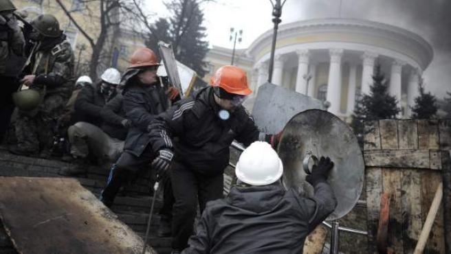 Activistas de la oposición se protegen con escudos durante los enfrentamientos con la policía en la Plaza de la Independencia en Kiev (Ucrania).