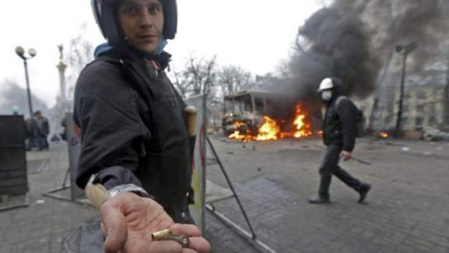 Un manifestante muestra dos balas durante los enfrentamientos con los antidisturbios en la Plaza de la Independencia en Kiev.