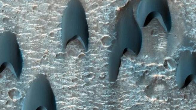 Formación dunar en Marte cuya forma recuerda al emblema de la famosa serie de ciencia-ficción Star Trek. La forma en uve de estas dunas recuerda también a la forma en la que vuelan las aves y la forma en la que se diseñan los aviones para optimizar el gasto energético.