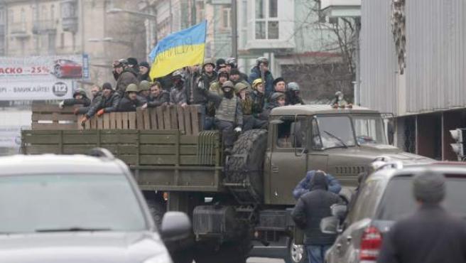 Un grupo de manifestantes opositores a Yanukovich ondea una bandera de Ucrania desde un vehículo militar en pleno centro de Kiev, la capital del país.