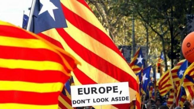 Banderas catalanas en una manifestación independentista junto a una pancarta que reclama a Europa que no mire para otro lado.