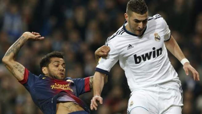 El brasileño Dani Alves intenta quitar el balón a Benzema durante un Real Madrid - Barcelona.