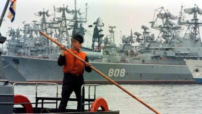 Un marinero en un barco patrulla cerca de un buque de guerra ruso atracado en el puerto de Sebastopol, Crimea (Ucrania).