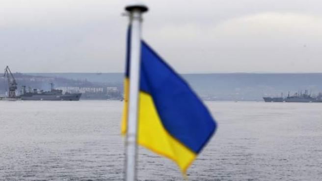 Un barco ruso (derecha) y uno ucraniano (izquierda), frente a frente en el puerto de Sebastopol, con la bandera ucraniana en el centro.