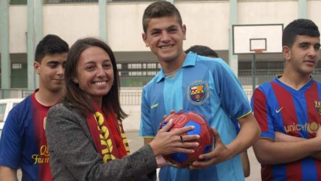 La periodista Ana Alba, en representación del FC Barcelona, entrega un balón a un niño palestino.