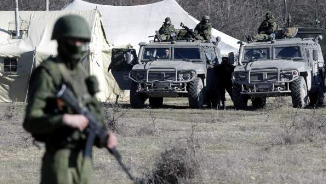 Soldados armados sin identificar, presuntamente rusos, vigilan el territorio de una unidad militar ucraniana, en la localidad de Perevalnoyea, a las afueras de Simféropol, en la península ucraniana de Crimea.